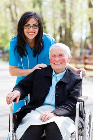 Beautiful doctor, nurse in blue coat walking a kind elderly lady in wheelchair in park.