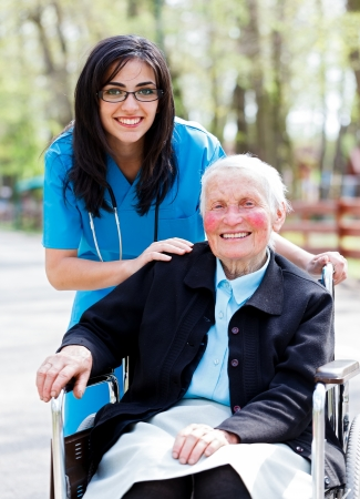 Kind doctor, nurse outdoors taking care of an ill elderly woman in wheelchair.