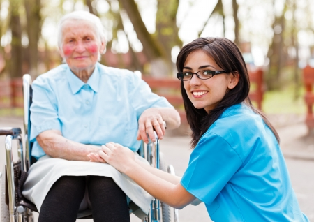 Kind doctor, nurse outdoors taking care of an ill elderly woman in wheelchair. Stock Photo - 20796368