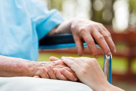 Arts die ouderen de hand patiënt in een rolstoel.