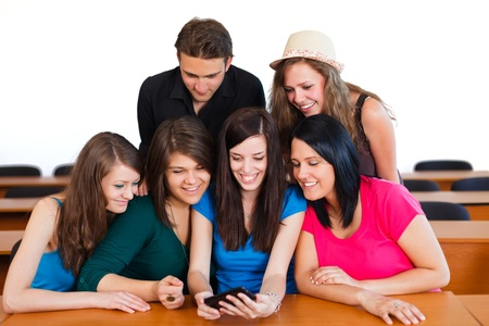 class room: Smiling students looking at classmates new smart phone. Stock Photo