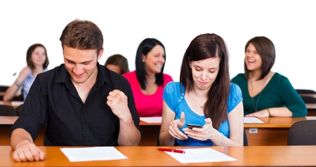 finals: Boy excited about successful finals, girl texting the results in classroom.