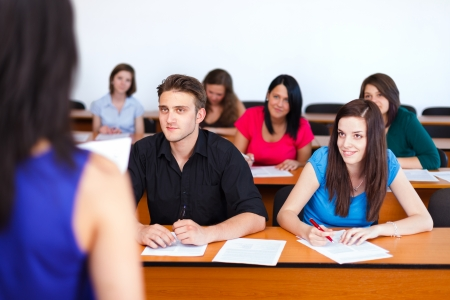 final examination: Kind students looking attentively at their teacher. Stock Photo