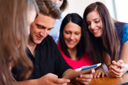 multinational: Happy smiling students together using touchscreen tablet. Stock Photo