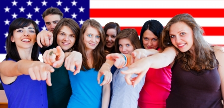 Happy young people in front of American flag point. Stock Photo - 20797207