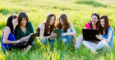 Girlfriends having fun outdoors using wireless internet on their laptops and tablet. photo