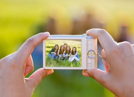 group picture: Lady hands taking photo of the group sitting on grass - groupphoto series. Stock Photo