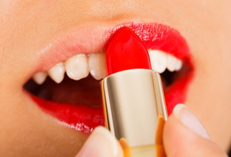 pintalabios: La aplicaci�n de brillo de labios rojos suavemente en los labios seductores. Foto de archivo