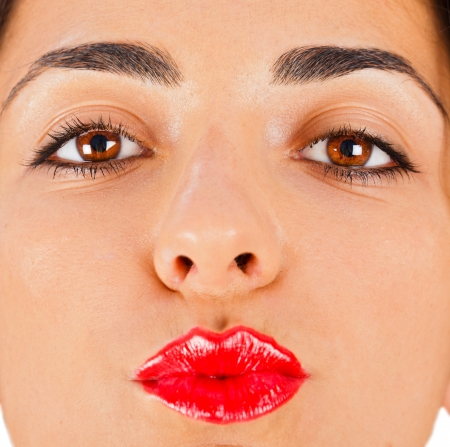 Beautiful brunette woman with red lipstick on sending kisses. photo