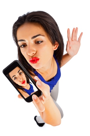 selfie: Beautiful girl making duck face taking selfportrait with her smart phone. Stock Photo