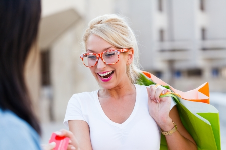 Very happy blond woman holding shopping bags paying. Stock Photo - 21145800