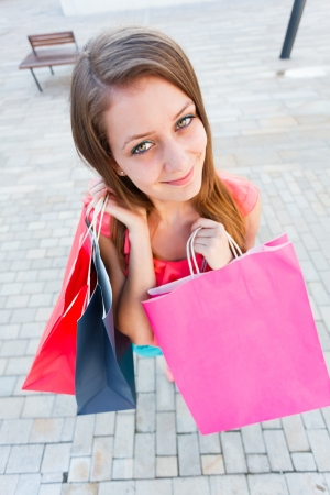 carelessness: Happy young woman with lot of shopping bags.