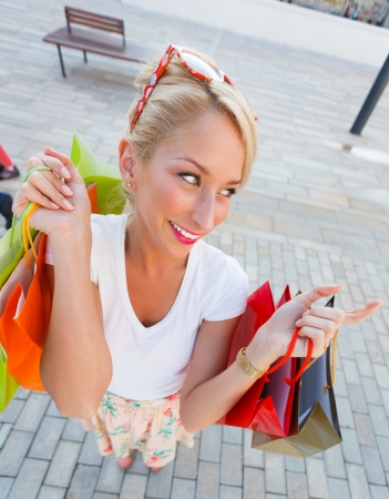 Gorgeous young woman smiling with shopping bags - wide angle. Stock Photo - 21145813