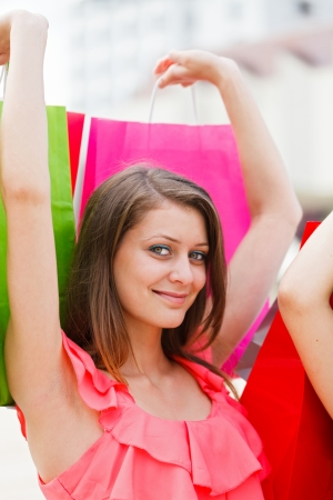 carelessness: Attractive young woman with cute smile holding several shopping bags. Stock Photo
