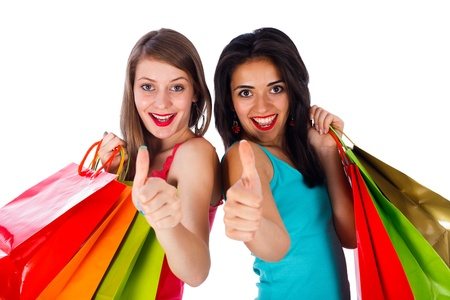 Ladies with shopping bags showing thumbs up - isolated on white. Stock Photo - 21460982