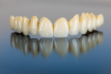 prosthesis: Beautiful ceramic teeth made in the dentist s office on mirror surface.