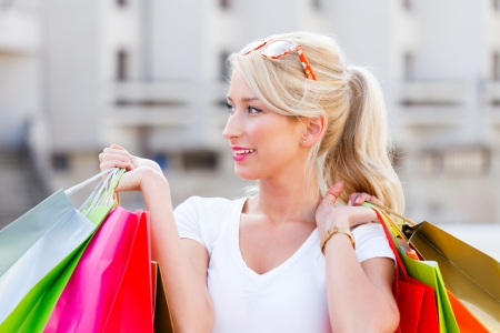 kindly: Beautiful woman smiling kindly holding shopping bags in the city center. Stock Photo