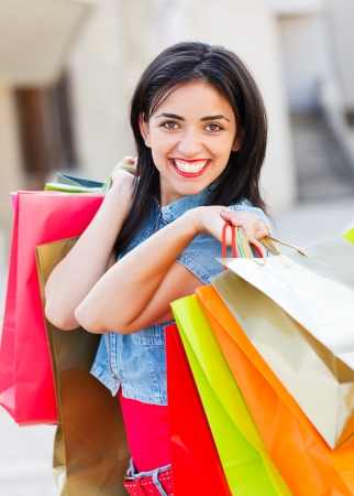 Gorgeous young lady holding shopping bags and smiling. Stock Photo - 21828824