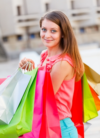 joyfully: Gorgeous woman holding shopping bags and smiling joyfully after a shopping.