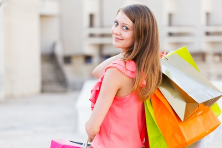 Gorgeous young lady holding shopping bags and smiling. Stock Photo - 21829097