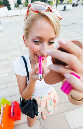 Attractive blond girl coming from shopping applying lipstick - wide angle. 版權商用圖片