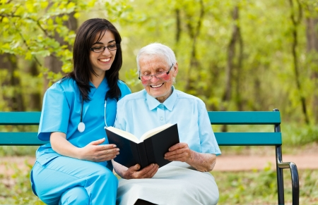 Caring doctor with kind elderly lady sitting on a bench reading a book. Stock Photo
