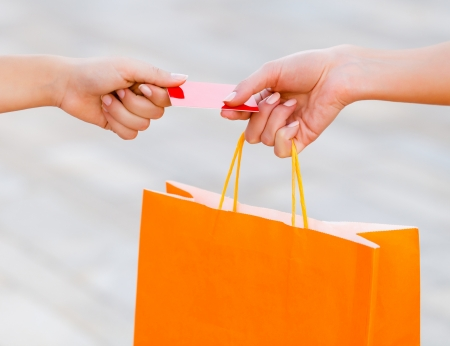 Woman holding an orange bag and paying with credit card. Stock Photo - 21829108
