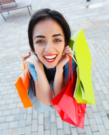 Girl very excited about shopping holding many shopping bags. Stock Photo - 21829452