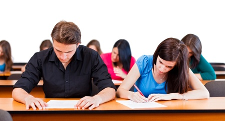 Students at university writing test in classroom.