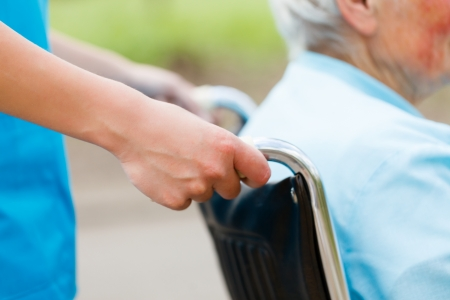 old age home: Elderly woman in wheelchair pushed by nurses hands. Stock Photo