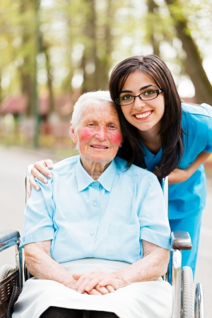 Kind elderly lady in wheelchair with a nice nurse next to her out in park.
