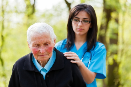 Kind nurse in blue consoling sad senior patient.
