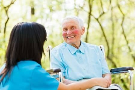 old age home: Happy elderly lady in wheelchair smiling kindly while talking with nurse. Stock Photo