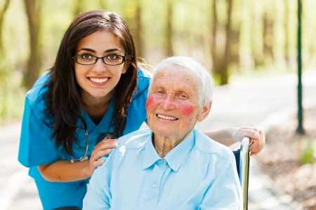 Vriendelijke verpleegster en gelukkig bejaarde petient samen buitenshuis.