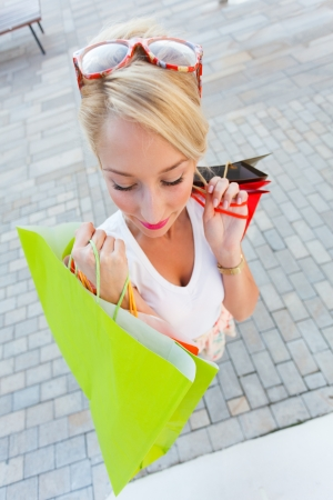 Cute girl out shopping in the city with many shopping bags. Stock Photo - 21829710
