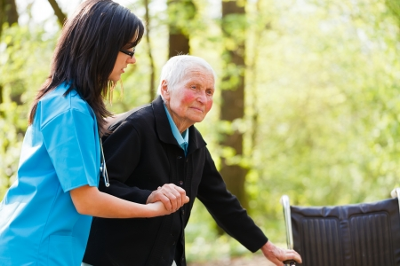 Caring nurse or doctor helping elderly patient to sit down on her wheelchair.
