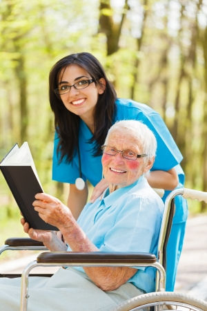 Kind nurse and elderly lady in wheelchair outdoors reading a book. photo