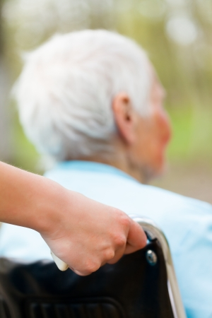 Nurse pushing wheelchair outdoors with senior patient.