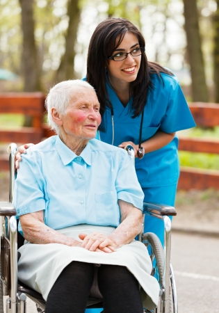 Elderly lady and nurse looking at the arriving visitors. photo