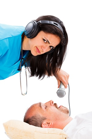 Doctor lady listening to a sleeping mans snoring - disturbing snoring concept. photo