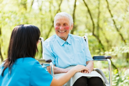 Happy elderly patient laughing and talking with caring nurse. photo