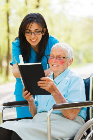 Elderly lady outdoors in wheelchair reading bible with nurse. Archivio Fotografico