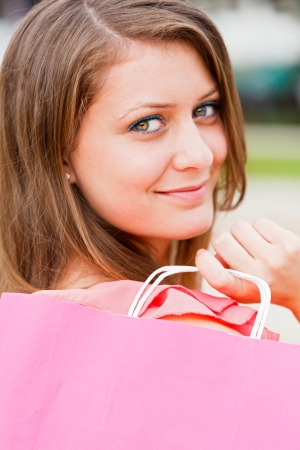 kindly: Attractive woman with shopping bag out in the city smiling kindly. Stock Photo