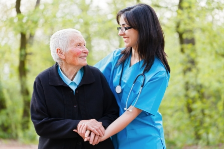Portrait of caring nurse and happy senior lady while  holding hands. Stock Photo