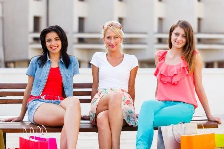 mujeres fashion: Tres hermosas mujeres en la ciudad que se sientan en un banco y sonriente.