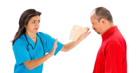 Doctor handing handkerchief to a sneezing man - isolated on white. photo
