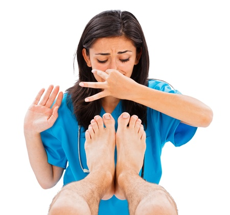 smell: Female doctor holding her nose not to smell the mans stinky feet - isolated image.