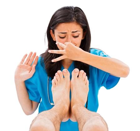 pies masculinos: M�dico mujer sosteniendo su nariz para no oler los pies apestosos del hombre - imagen aislada.