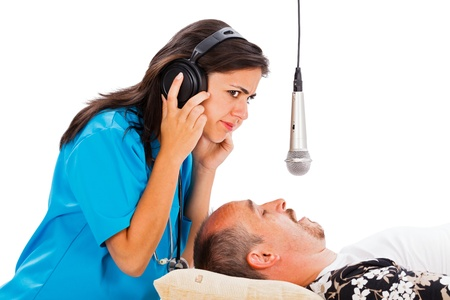 Doctor lady listening to a sleeping mans snoring - disturbing snoring concept. Stock Photo