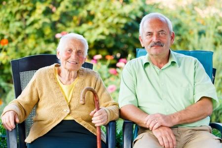 Moeder en zoon zitten op stoelen in de tuin van het verpleeghuis.